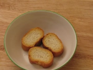 Toast baguette slices and then place in heat-proof bowl.