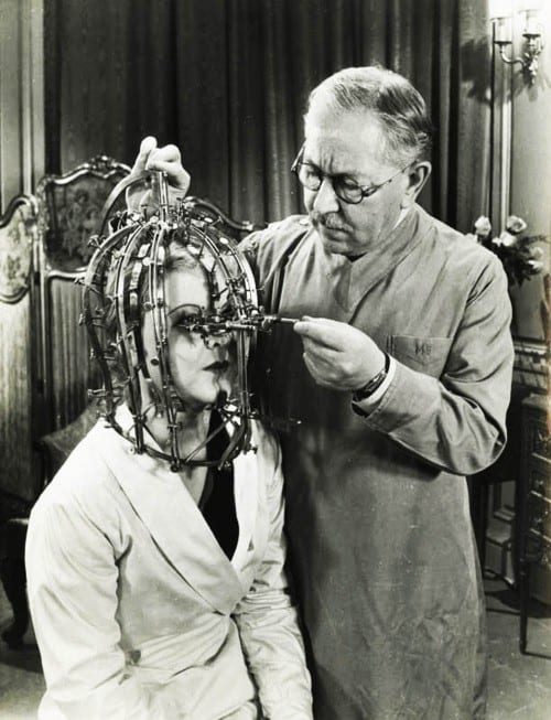 """1934 Max Factor demonstrates his """"scientific device"""" the Beauty Micrometer which detects defects in feminine beauty that are imperceptible to the naked eye. Image courtesy of FilmMakerIQ.com"""
